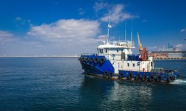 Towing ship in the open sea, blue tugboat sailing on sea stock photo