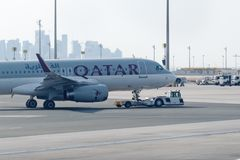 Towing tractor pushing airplane by Qatar airline on Doha International airport. stock photo