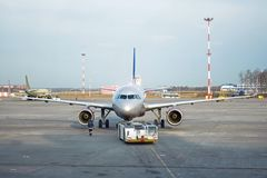 Towing truck pushing back passenger airplane business jet to the Stock Photo