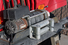 A towing winch on a jeep. Is being used to pull another vehicle. A winch is a stationary hoisting machine having a drum around which is wound a chain attached stock image