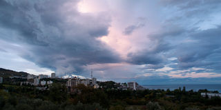 Town at black see. clouds covering sky at sun set. Sun set at black sea with town under cloudy heaven stock photography