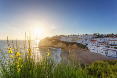 The town of Carvoeiro at sunset. Tourists are walking along beach. Royalty Free Stock Photo