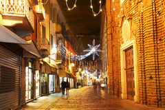 Town center at evening. Alba, Italy. Alba old town central street with opened shops, bars and stores and illuminations for Christmas and New Year holidays Royalty Free Stock Photo