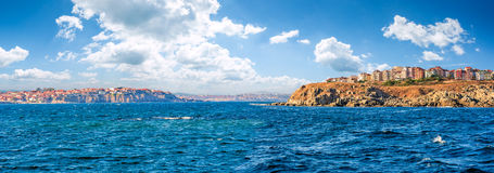 Town on a cliff above the seashore. Composite summer seascape. panoramic view of old resort town on a rocky cliff above the seashore. blue and calm water in the stock photography