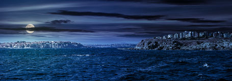 Town on a cliff above the seashore at night. Composite summer seascape. panoramic view of old resort town on a rocky cliff above the seashore. blue and calm royalty free stock image