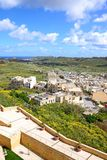 Town and countryside seen from the citadel, Gozo. Elevated view of fortified buildings and the landscaped old moat within the citadel with views over the town Stock Image