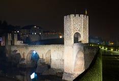 Town with gate on bridge in night.  Besalu Stock Photo