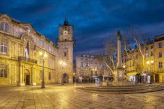 Town Hall square at dusk in Aix-en-Provence, France. Town Hall square at dusk with City Hall Hotel de Ville building, clock tower and fountain in Aix-en-Provence Stock Images