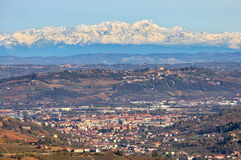 Town among hills and snowy mountain peaks on background. Royalty Free Stock Images