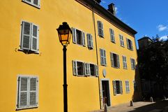 Town house in Sion. Town house with yellow walls and street lamp in Sion Switzerland. Over the entrance door is the coat of arms of the state of Valais Stock Photography