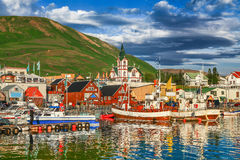 Town of Husavik at sunset, north coast of Iceland. Beautiful view of the historic town of Husavik in golden evening light at sunset, north coast of Iceland royalty free stock photography