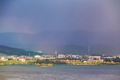 Town on the lake behind the foothills. Spring rain and storm in Royalty Free Stock Image