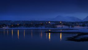 Town with lights and reflections in fjord, during Arctic night Royalty Free Stock Image