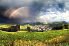 Town in mountain valley under rainbow and stormy clouds Stock Image