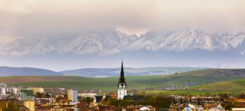 Town and peak of cathedral tower behind snow-caped mountains Stock Images
