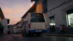 Town Road At Dusk With Passing Bus. Kids run across road and bus passes in old part of town at sunset stock video