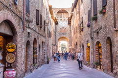 Town of San Gimignano, Italy. San Gimignano, Italy - Oct 3, 2016. People visiting the old town of San Gimignano with many interesting shops on the street Stock Image