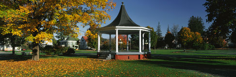 Town square. This is the town square. In the center is a gazebo. It is located on Main Street. There is autumn foliage in a park setting. We see Victorian style Stock Images