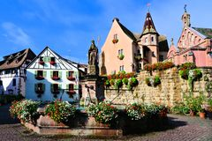 Town square in the Alsace village of Eguisheim, France. Beautiful town square in the Alsace village of Eguisheim with fountain, castle and church, France Royalty Free Stock Image