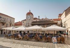 Town square in Trogir. Trogir, Croatia - August 6, 2012: Main town square in historic center of Trogir with San Sebastian church clock tower and people sitting Royalty Free Stock Image