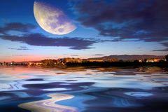 Town at sunset. With moon and reflection Stock Photos