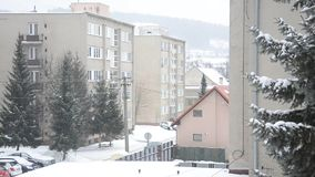 Town in winter, it snows at street, flat houses, trees and cars, some walker goes on footpath stock footage