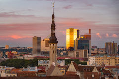 Townhall and modern buildings against sunset sky, Tallinn. Townhall and modern buildings against colorful sunset sky, Tallinn, Estonia Royalty Free Stock Photos