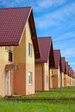 Townhouses with household lawns. Condo for sale arranged in a row. Undeveloped gardens Stock Images