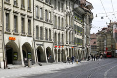 Townhouses and visible arcades in Bern. Bern, Switzerland - April 17, 2017: Townhouses and visible arcades along the street on which you can see the tram rails Royalty Free Stock Photography