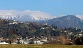 Townscape av Tarcento, nära Udine i Italien, på dess kullar På bakgrund den snöade Julian Alps Arkivbild