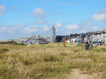 Townscape Katwijk aan Zee with Church, dwellings and dunes with grass. Townscape boulevard Katwijk aan Zee with white Protestant Church, dwellings and dunes with stock photo