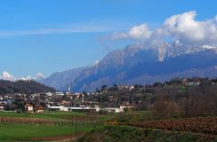 Townscape of the village of Buja, near Udine in Italy, under the beautiful scenery of the Julian Alps on an early spring day. In the autonomous region of Friuli Royalty Free Stock Photos