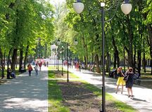 Townsfolk having a walk in the city park at a sunny feast day Stock Image