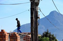 Township Builder. A brick layer walks on the roof of a township shack against a mountain in Masiphumelele Township, Cape Town, South Africa stock photography