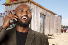 Township businessman. Black South African man on phone with a container spaza shop in a township in the background royalty free stock photos
