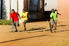 Township Sports - Tyre Race. Group of Boys Playing with wheel rim of a bicycle and a loose tyre Stock Image