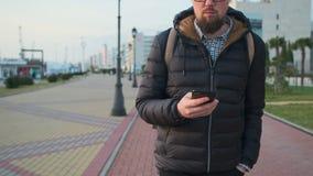 Townsman идет на пешеходную зону города во дне осени, держа смартфон сток-видео