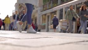 Townspeople are walking over street and city square in sunny spring day, view from ground, blurred shot. Tourists and citizens stock video footage