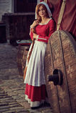 Townswoman στο κόκκινο φόρεμα με μια ποδιά και chaperone στην οδό στοκ φωτογραφίες