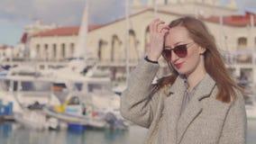 Townswoman гуляет на тропе в порте около современных яхт в солнечной весне сток-видео