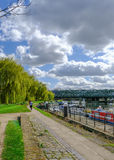 Towpath with joggers by River Lea, Bow. London. Shows willow trees and railway bridge in spring royalty free stock images
