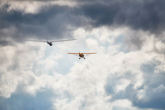 Towplane with a sailglider makeing their way into the cloudy sky. Stock Photography