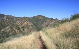 Towsley Canyon Panorama. Trail through a field with mountains and sky, California Royalty Free Stock Photo