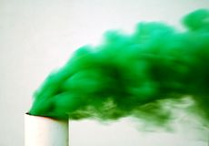 Toxic Blow. Green smoke blows hard into the atmosphere from a pipe royalty free stock image