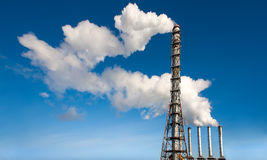 Toxic industrial smoke from chimney on blue sky Stock Photography