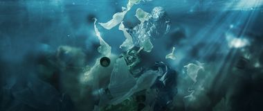 Toxic plastic waste floating underwater in the ocean royalty free stock photo
