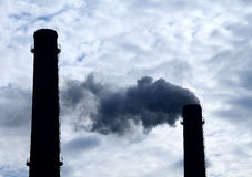 Toxic smoke pollution from smokestack over cloudy sky Stock Photo