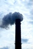 Toxic smoke pollution from smokestack over cloudy sky Royalty Free Stock Images