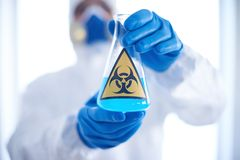 Toxic substance. Gloved scientist hands with flask containing blue toxic fluid stock photography