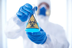 Toxic substance in tube. Gloved scientist hands holding glass tube with toxic fluid Royalty Free Stock Images